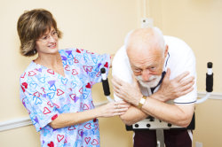 staff assisting her patient in exercise